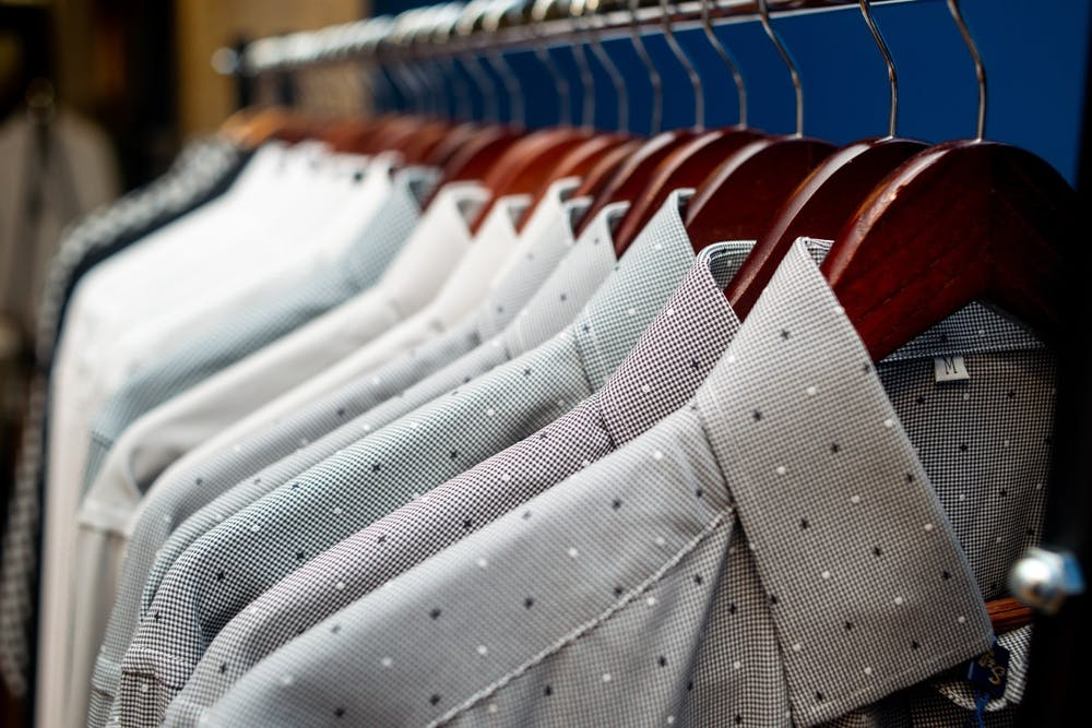 <p>Dress shirts line the racks June 10, 2019 at State and Liberty Clothing in Ann Arbor, Michigan.</p>