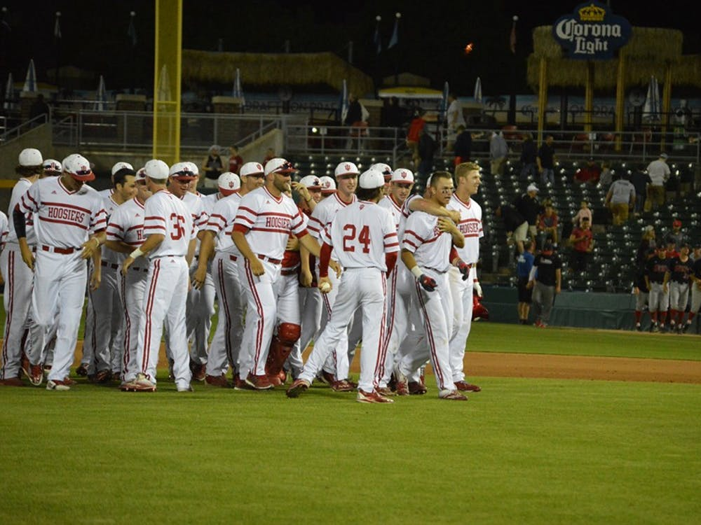Teammates throw thier arms around Freshman Matt Gorski's neck and congratulate him for his game winning hit Tuesday night. After 10 innings the Hoosiers beat Ball State 4-3.