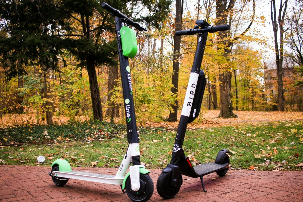 <p>A Bird and Lime scooter are set across from each other in front of Dunn&#x27;s Woods. This spring, scooters from the Midwestern-based company VeoRide will join Bird and Lime scooters on the streets and sidewalks of Bloomington.</p>