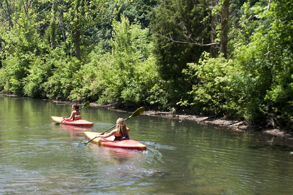 <p>Then-senior Kayla Rhodes and then-junior Amy DiMatteo paddle their kayaks away from shore at Griffy Lake in 2009. Griffy Lake is one of several options for dog owners in Bloomington to take their pets.</p>
