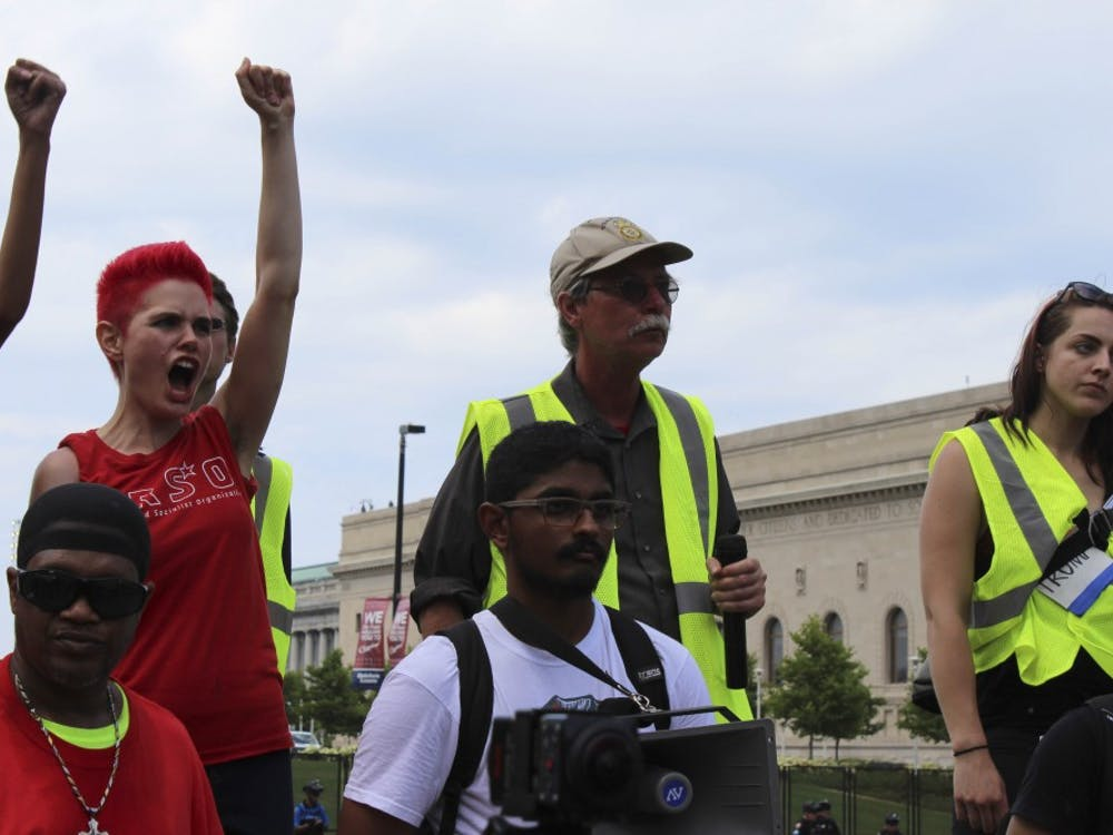 Kait McIntyre and other demonstrators raise their fists in the air, calling for equality for all in America.