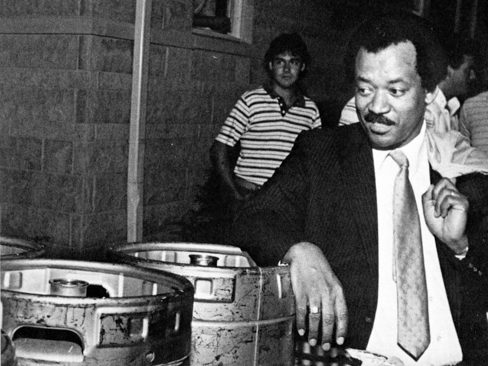 Former Dean of Students Michael Gordon glances over beer kegs confiscated at the Sigma Alpha Mu fraternity house during the first campus alcohol raid.
