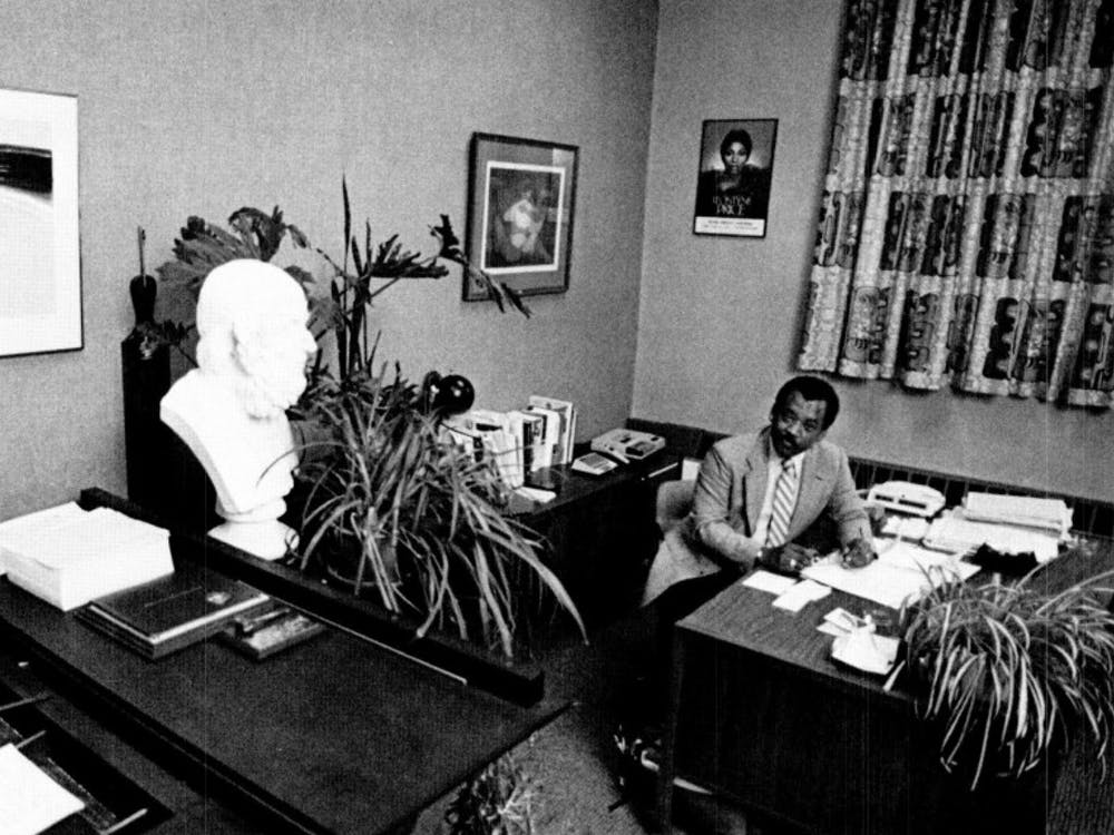 Former Dean of Students Michael Gordon sits in his office in 1984. Gordon had a piano in his office, seen in the lower lefthand corner, that he was known for playing.