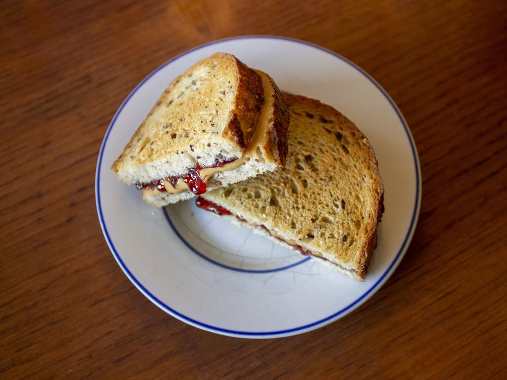 A peanut butter and jelly sandwich sits on a plate.
