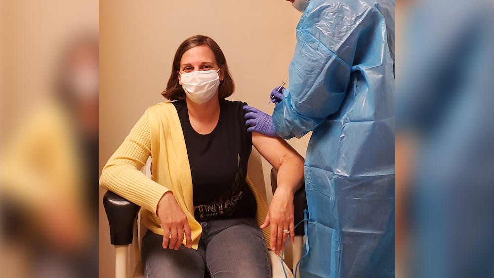 Nurse Valerie Geraghty gives a shot to COVID-19 clinical trial participant Amy Pegg.