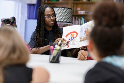 IU alumnus Tyler Kelley reads at the alumni chapter of Alpha Phi Alpha's weekly reading group at The Rise. Kelley started the program, which provides transitional housing and resources for families affected by violence.