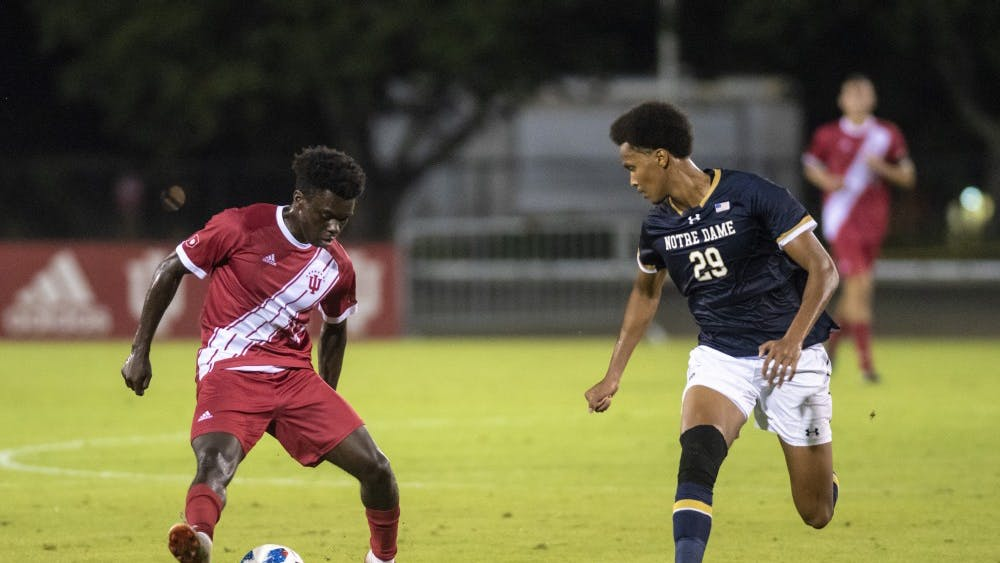 Freshman Herbert Endeley steps over the ball as University of Notre Dame sophomore Mohamed Omar follows Sept. 17 at Bill Armstrong Stadium. Endeley scored the equalizing goal for IU in the second-half of the match.