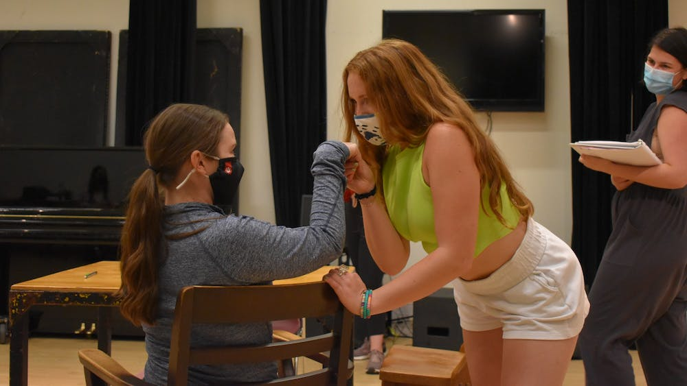 """IU senior Sophia Salesky kisses the hand of master of fine arts candidate Leah Mueller during rehearsals for """"The Well of Horniness"""" on Sept. 8, 2021, at the Lee Norvelle Theatre and Drama Center. As a queer comedy, the show satirizes many genres heterosexual men traditionally dominate."""