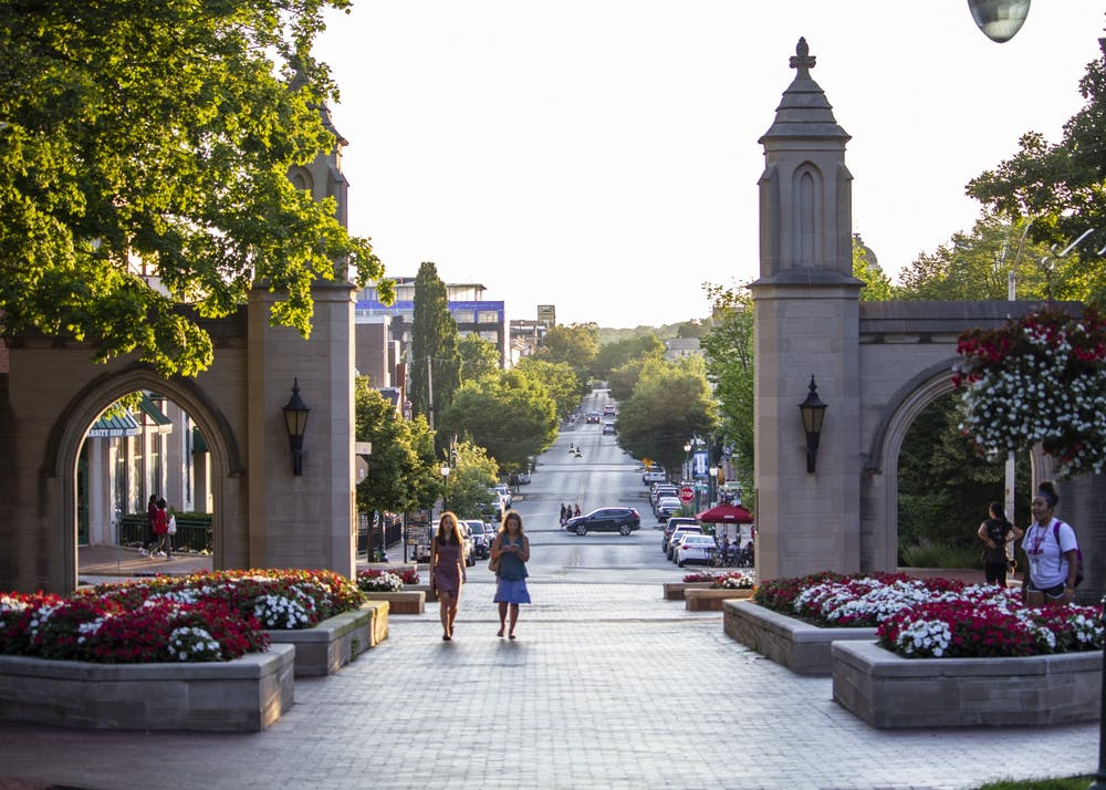 <p>People walk through the Sample Gates on June 27, 2018, near Franklin Hall. IU announced Monday undergraduate students are eligible to take one online course per semester from six other schools in the Big Ten Academic Alliance during the 2020-21 academic year.</p>