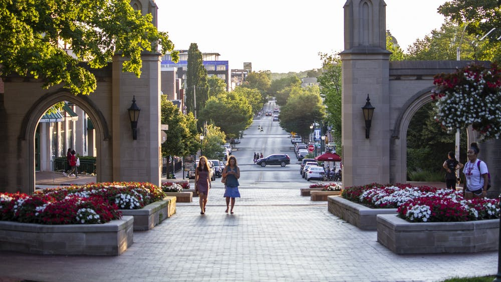 People walk through the Sample Gates on June 27, 2018, near Franklin Hall. IU announced Monday undergraduate students are eligible to take one online course per semester from six other schools in the Big Ten Academic Alliance during the 2020-21 academic year.