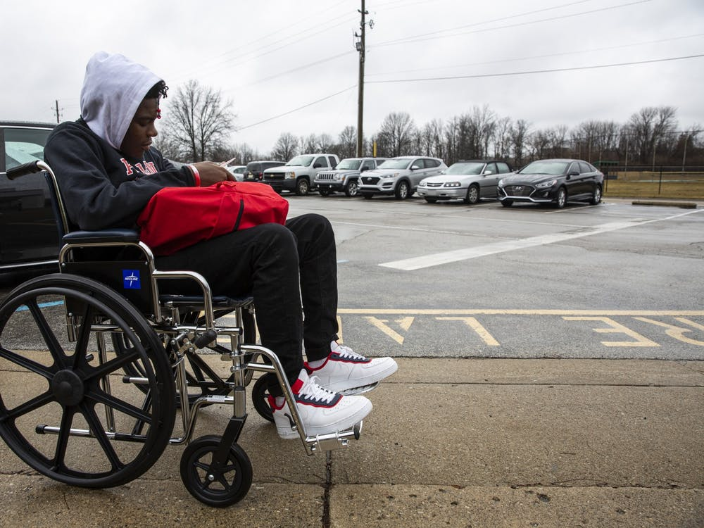 "Da'Quincy Pittman waits in a wheelchair for his mother to pick him up after his first day back. The wheelchair was a precaution since he still felt lightheaded after collapsing. ""It was just like everything shutting down on me,"" he said."