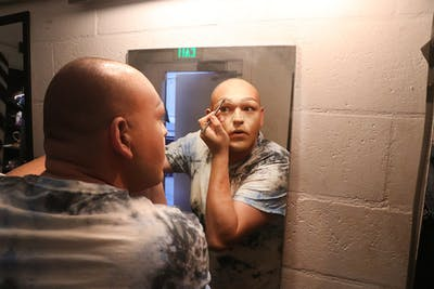 Billy Vorgias prepares for his performance backstage by applying makeup. It takes Vorgias approximately two hours, 45 minutes of that for makeup alone, to transform into Envy T. Debeauté.