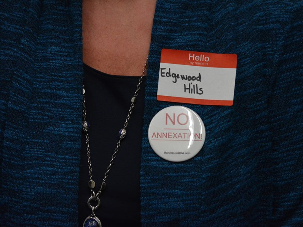 Alison Evans, a resident of Edgewood Hills in annexation area two, wears a pin to protest the proposed new boundaries of Bloomington. Evans was one of about 50 township residents who came Wednesday night's city council meeting.