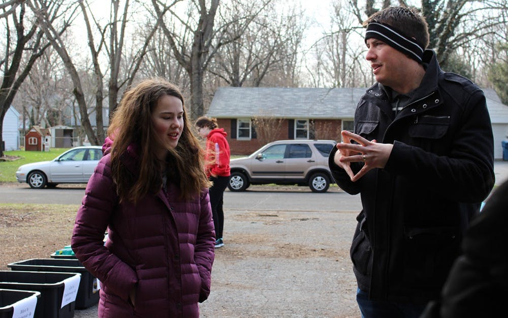 Chris Vermilion and his daughter, Emma, huddle in the cold of their driveway, where people have brought supplies for refugee families. Chris and his wife, Traci, started the Indiana Refugee Network together.