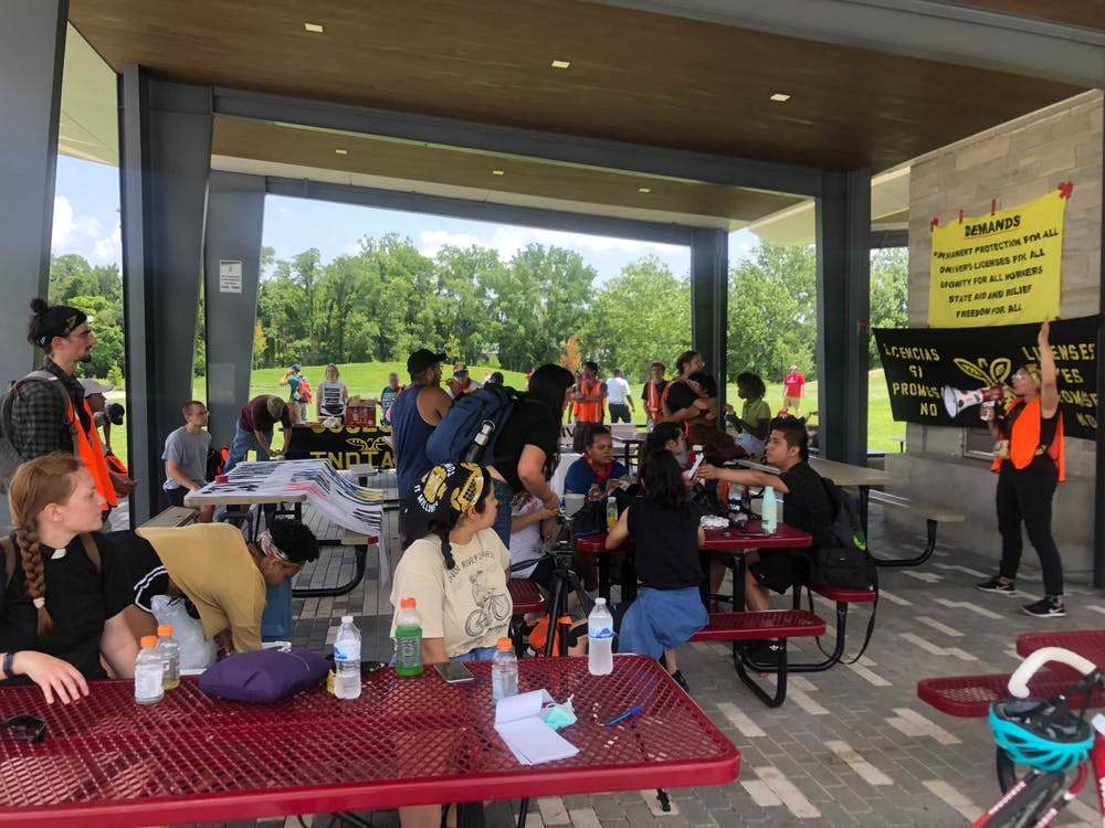 <p>Members and allies of Cosecha Indiana eat and hydrate under a pavilion at Switchyard Park in Bloomington Thursday in preparation for their walk to Sample Gates. The group was gathered in support of undocumented immigrants who cannot obtain a driver&#x27;s license in Indiana.</p>