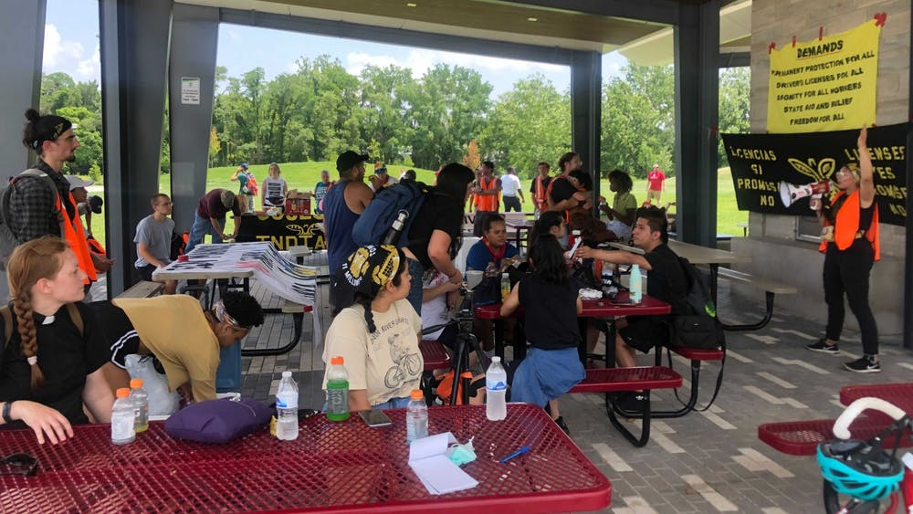 Members and allies of Cosecha Indiana eat and hydrate under a pavilion at Switchyard Park in Bloomington Thursday in preparation for their walk to Sample Gates. The group was gathered in support of undocumented immigrants who cannot obtain a driver's license in Indiana.