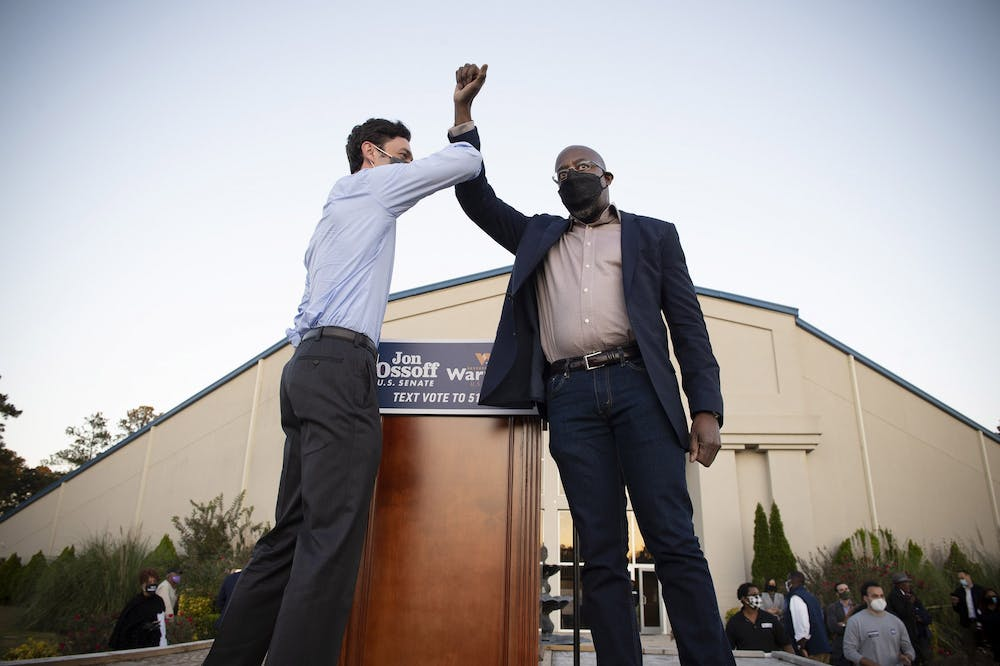 Democratic candidates Jon Ossoff, left, and the Rev. Raphael Warnock bump elbows Nov. 19 on stage at a rally in Jonesboro, Georgia.