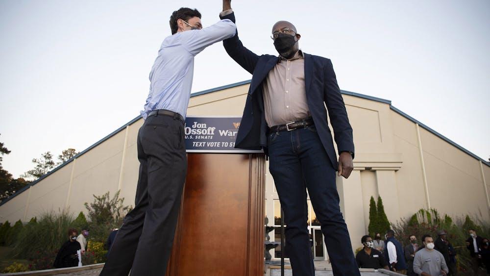 Democratic candidates Jon Ossoff, left, and the Rev. Raphael Warnock bump elbows Nov. 19 on stage at a rally in Jonesboro, Georgia.