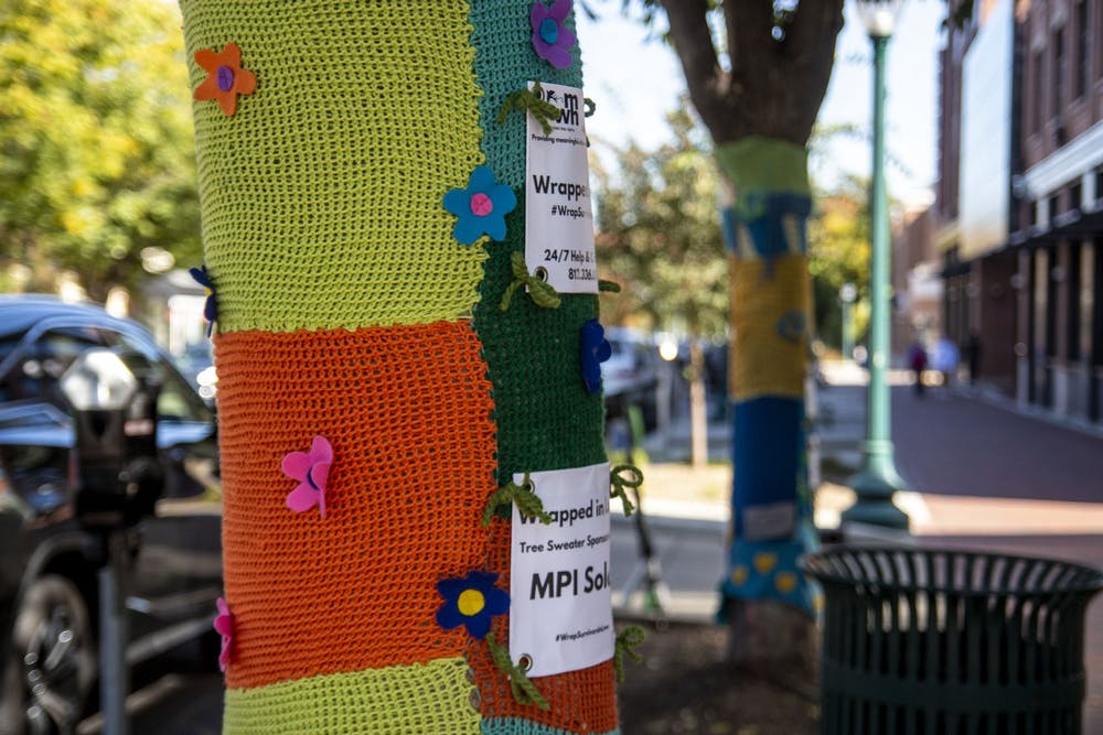 <p>Trees are seen wrapped in knit sweaters Wednesday on Kirkwood Avenue. The sweaters are a part of an over ten year tradition that supports the Middle Way House, and gives sponsors the opportunity to honor a person or organization, many of them survivors or victims of abuse.</p>