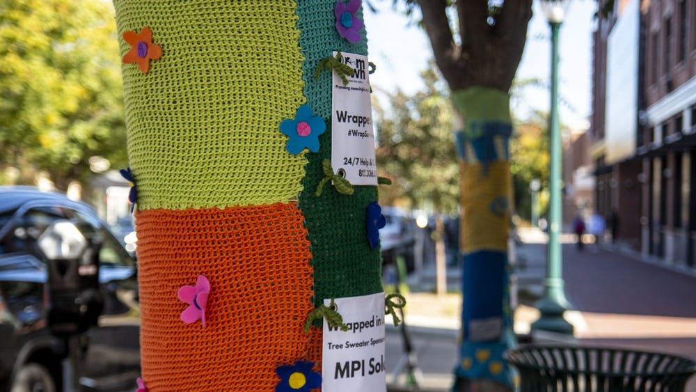 Trees are seen wrapped in knit sweaters Wednesday on Kirkwood Avenue. The sweaters are a part of an over ten year tradition that supports the Middle Way House, and gives sponsors the opportunity to honor a person or organization, many of them survivors or victims of abuse.