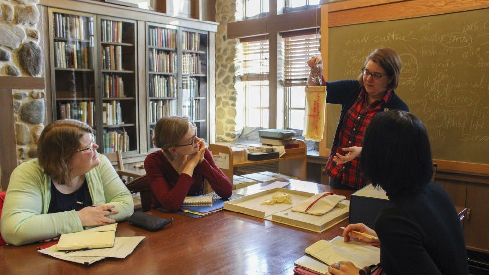 """Rebecca Baumann holds up a piece of latex with words printed on it from the book """"Lay Text."""" Seeing and discussing different types of books is part of a class called Z681: The Book 1450 to the Present, which is taught at the Lilly Library."""