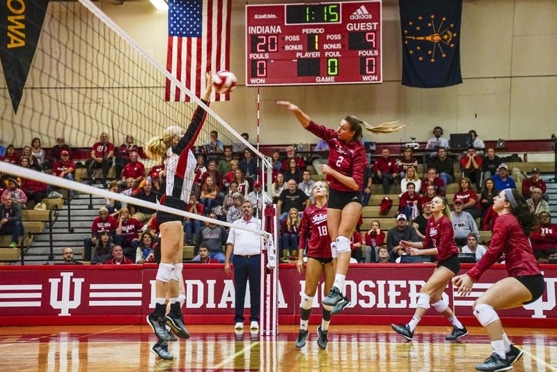 Junior middle blocker Hayden Huybers returns the ball against a Rutgers defender Oct. 13 in University Gym. IU defeated Rutgers, 3-0.
