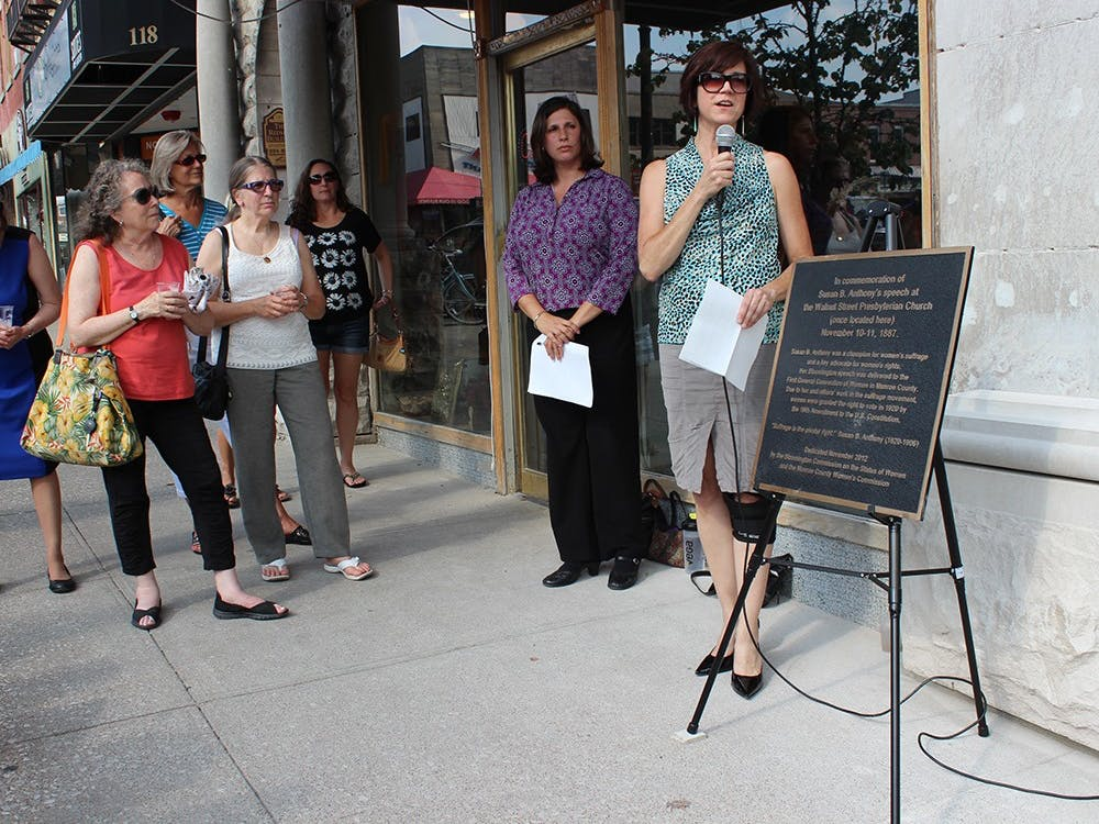 Cathi Crabtree, chair of the City of Bloomington Commission on the Status of Women, helps rededicate a plaque in memory of Susan B. Anthony's visit to Bloomington during the Women's Suffrage Movement.