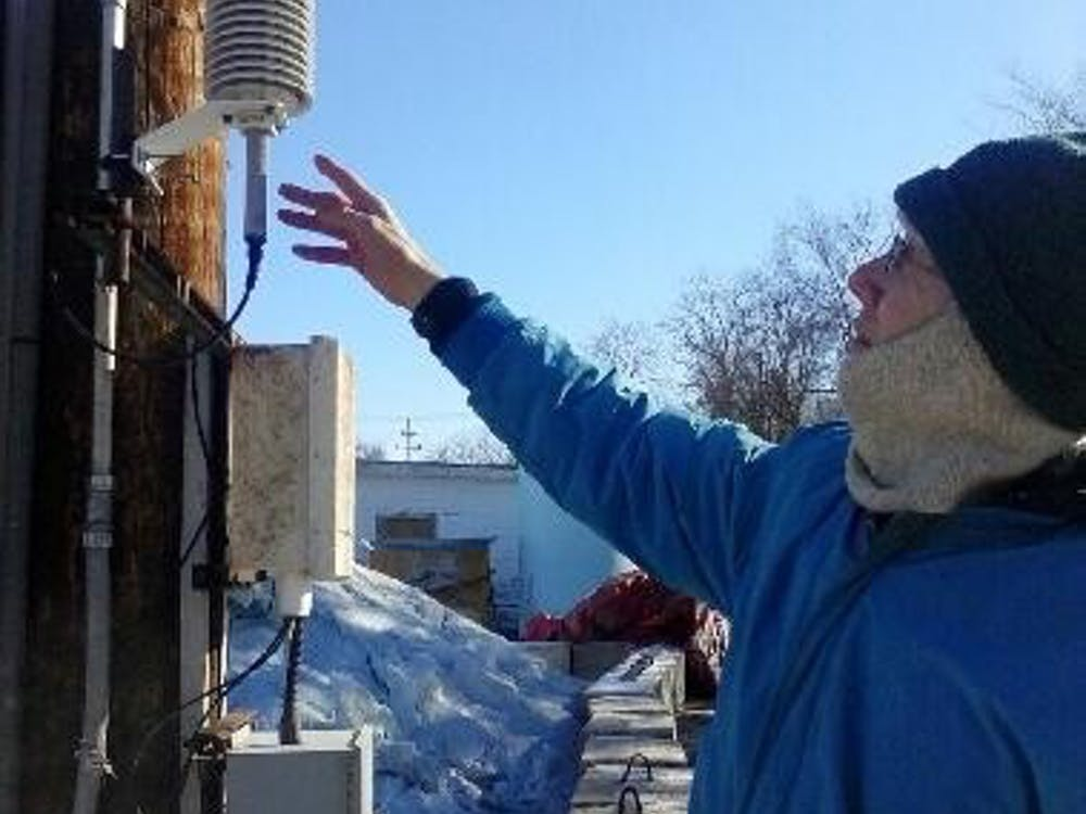 Master Electronics Technician Greg Gember explains the parts of the weather station on East Tenth Street Monday.