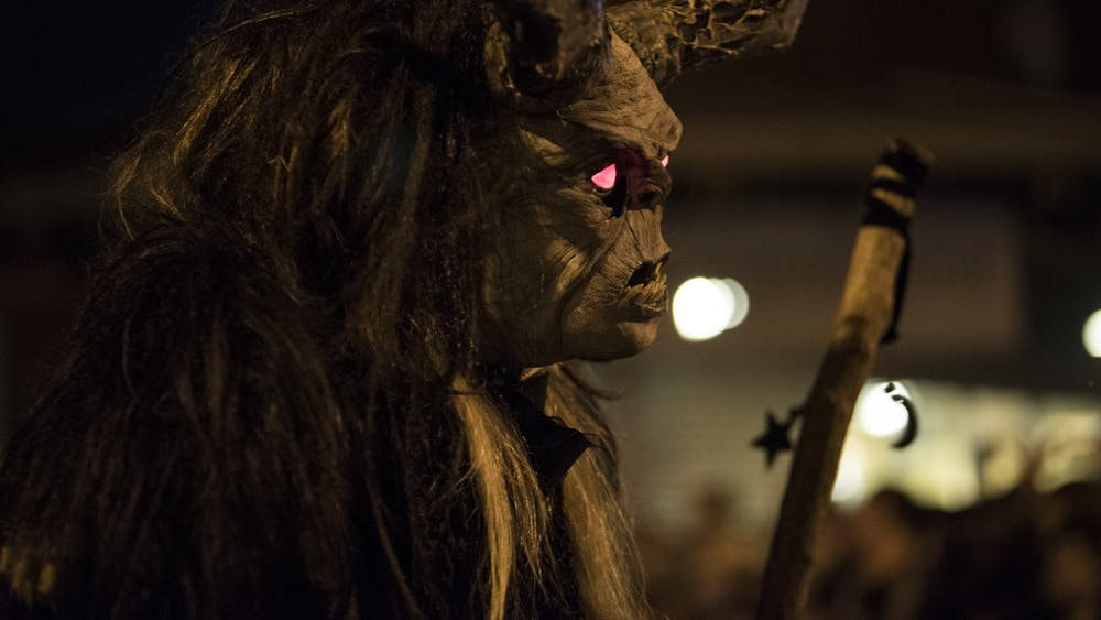 A person dressed as Krampus with glowing red eyes runs at children with a giant stick Dec. 2, 2017, at the Krampus Rampage and Bazaar.