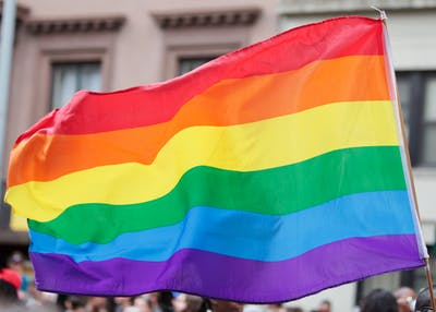 A rainbow flag symbolizing and celebrating gay rights and freedom of expression blows in the wind.