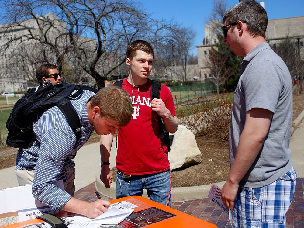 Freshman Collin Evans, left, signs up his name on the sign up sheet and senior Caleb Sperry listens about the purpose of the Empty Holster Protest from sophomore Miles Vining Wednesday right next to Wells Library. Students for Concealed on Campus at Indiana University was established in 2010 to spread awareness of the importance of freedom to carry handguns on the campus to protect themselves. The members protested by wearing a empty holster. The protest will be held until Apr.3.
