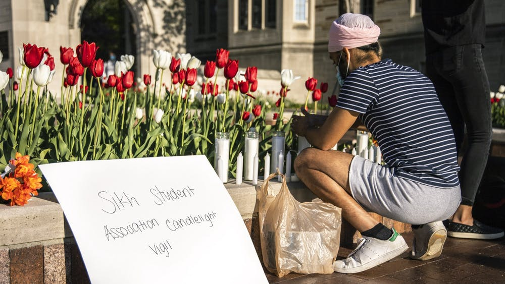 Freshman Mohkm Singh lights candles before the Sikh Student Association's vigil begins Sunday in front of the Sample Gates. The vigil was in honor of the victims of the Indianapolis FedEx shooting.