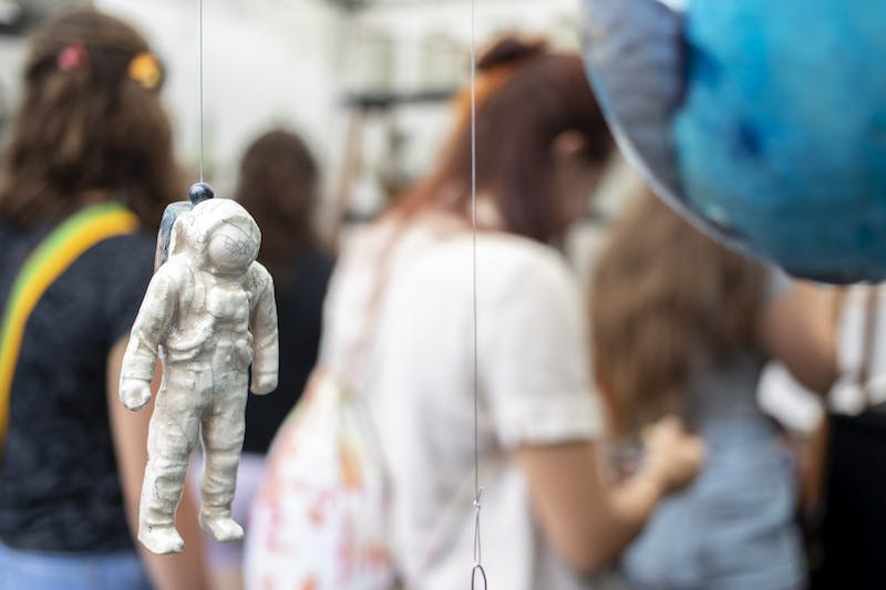 A ceramic astronaut hangs in Stan Baker's booth at Fourth Street Festival of Arts and Crafts on Aug. 30, 2019. The 2020 festival is now virtual, with showcases available online starting Saturday until Dec. 31.