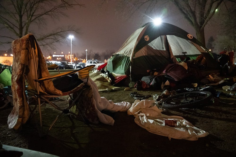 <p>Belongings of people experiencing homelessness lie in the grass on Monday at Seminary Park.</p>
