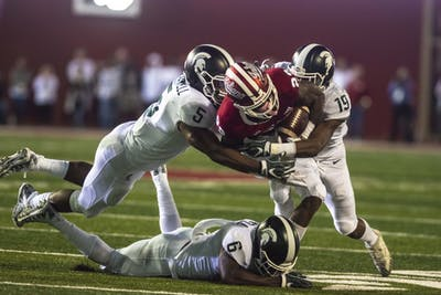 Sophomore wide receiver Whop Philyor is tackled by three Michigan State players during a game Sept. 22 at Memorial Stadium. IU was never able to overcome Michigan State's early lead.