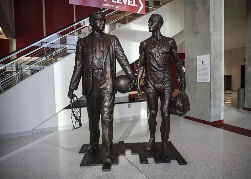 Two-time national champion Branch McCracken is depicted (left) alongside Bill Garrett, who became the first African-American to play Big Ten basketball in 1948. Garrett led IU in scoring and rebounding in each of his three seasons with the team and was named an All-American in his senior season. He was coached by McCracken, a former IU player himself, who led the team to two national titles while coaching the Hoosiers.