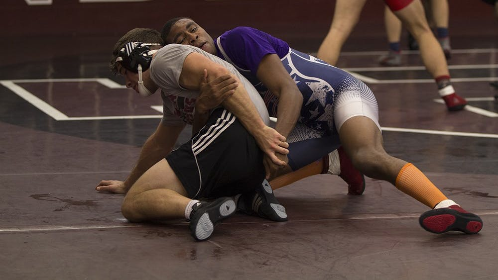Junior Nate Jackson tries to pin a teammate during practice on Nov. 4. Jackson dominated in the first meet of the season on Saturday.
