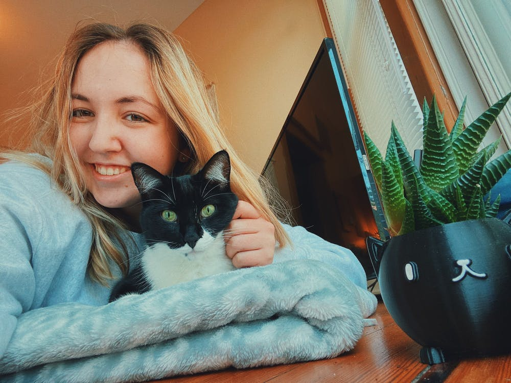 <p>Graduate student Lexi Haskell sits with her cat, Mo. Haskell contracted COVID-19 in September and has since recovered. </p>
