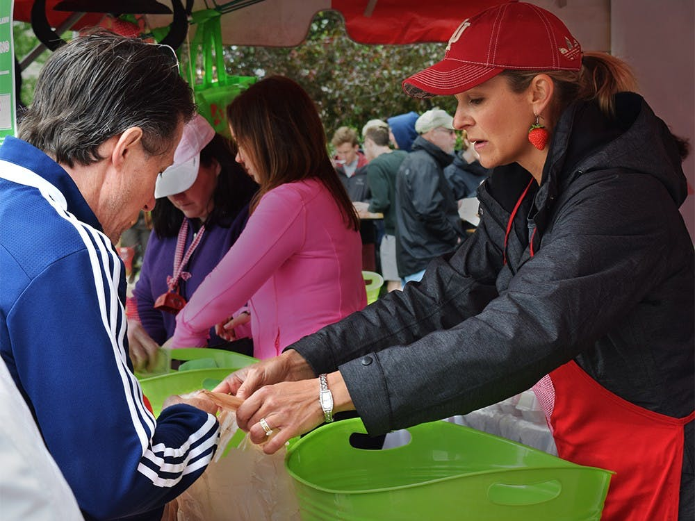 Krista Johns, co-chair of the Strawberry Shortcake Festival, sells Strawberry to customer during the Strawberry Shortcake Festival Thursday afternoon at Courthouse Lawn. This Festival celebrated a tradition 30 years.
