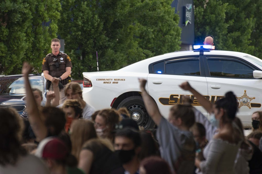 <p>A sheriff's car blocks traffic during a protest May 29 on North College Avenue outside the Charlotte T. Zietlow Justice Center in Bloomington. Protesters kneeled in silence for 7 minutes, some raised their fists.</p>