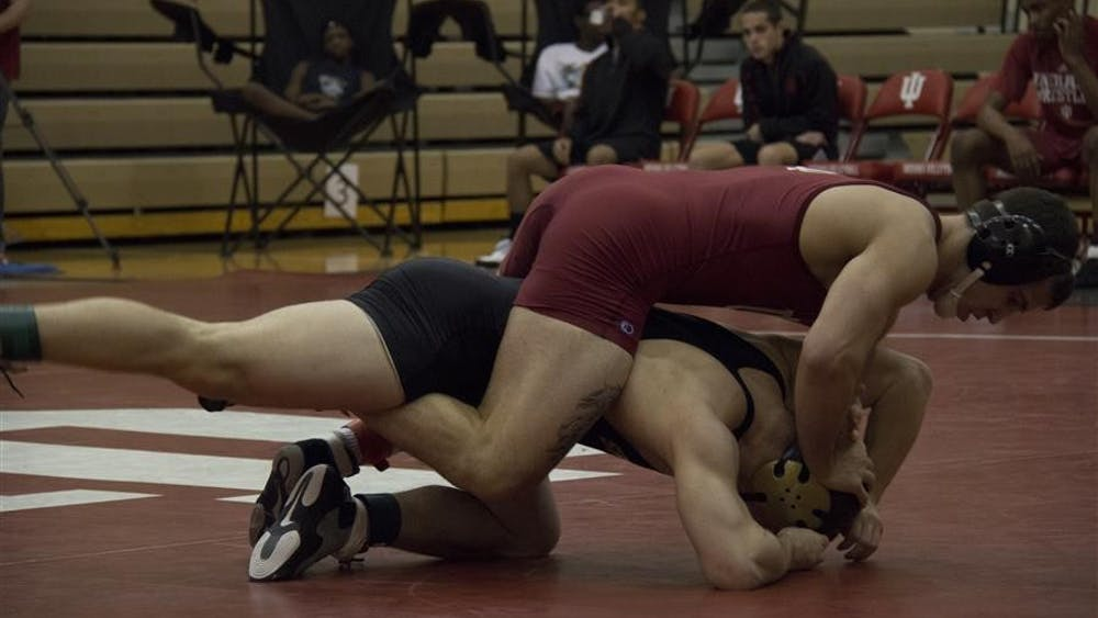 Junior Luke Sheridan wrestles his opponent during IU's match against Manchaster on Saturday in the University Gym. Sheridan defeated his opponent by pin.