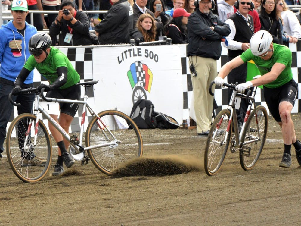 Sigma Alpha Epsilon exchanges bikes at the Men's Little 500 in 2017 at Bill Armstrong Stadium. Dirt from the track gets moved by the tire of one of the bikes, because of the dry track. Cyclists may prefer the track to be more wet for an easier and faster ride on the track.
