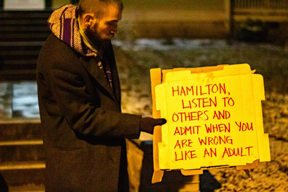 <p>Travis Dugan, 36, displays a sign at a protest on Jan. 17 referencing the recent evictions in Seminary Park. The city dismantled an encampment in the park Dec. 9, 2020, and Jan.14.</p>