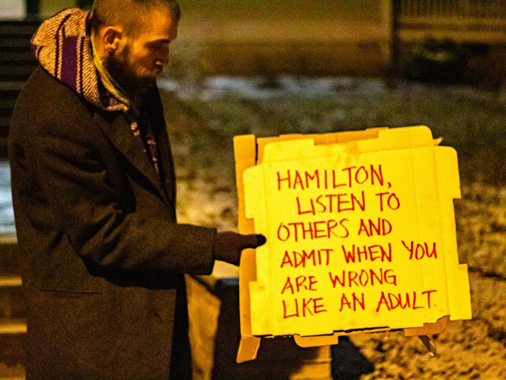 Travis Dugan, 36, displays a sign at a protest on Jan. 17 referencing the recent evictions in Seminary Park. The city dismantled an encampment in the park Dec. 9, 2020, and Jan.14.