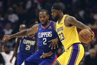 Los Angeles Lakers forward LeBron James dribbles around Los Angeles Clippers forward Kawhi Leonard Oct. 22, 2019, at Staples Center in Los Angeles.