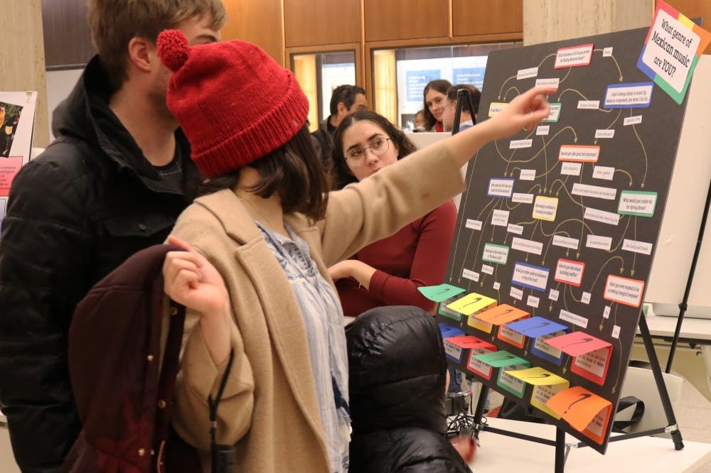 <p>Anna Ortega, an intern at the Latin American Music Center, watches as people interact with her booth at Exploremos on Feb. 7. The open house, located in the Herman B Wells Library, celebrated Mexican history and culture.</p>