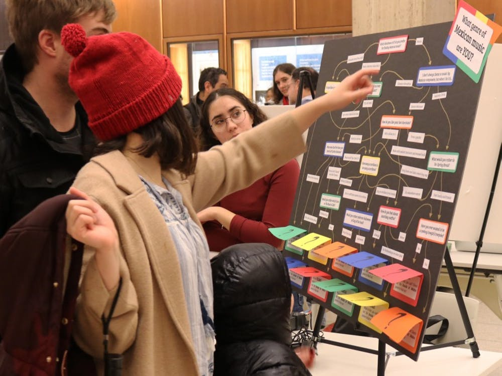 Anna Ortega, an intern at the Latin American Music Center, watches as people interact with her booth at Exploremos on Feb. 7. The open house, located in the Herman B Wells Library, celebrated Mexican history and culture.