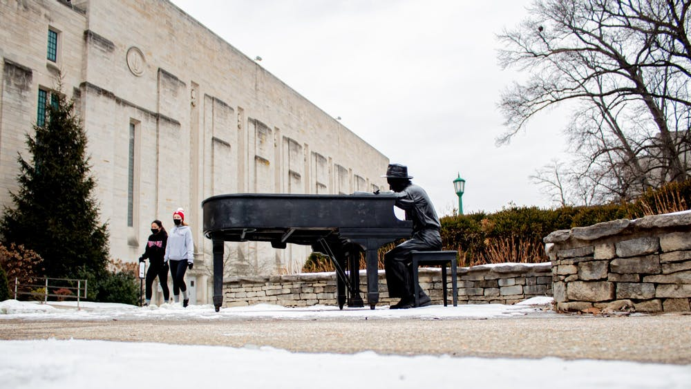 Students walk Monday by the Hoagy Carmichael sculpture outside of the IU Auditorium. Temperatures are expected to reach a low of -4 degrees in Bloomington this week.