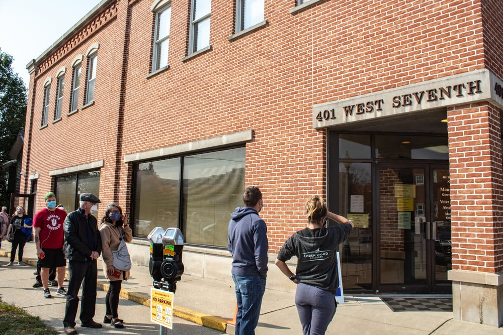 <p>Voters wait in line to vote Oct. 6 at Election Central at 401 W. Seventh St. Voters said wait times were roughly an hour despite the long line on the first day of early voting in Indiana.</p>