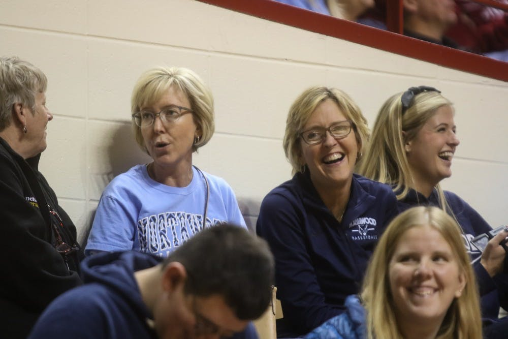 """Mary Tydall, left, and Cathy German, right, are the granddaughters of Emmett """"Branch"""" McCracken. They attended Friday's women's basketball game to watch Cathy's daughter, Grace, play on the court named after their grandfather."""